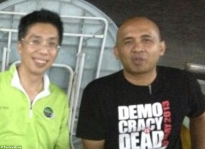 Peter Chong (left) with best friend Captain Zaharie Ahmad Shah, pilot of the missing Malaysia Airlines plane. He is pictured in a T-shirt with a Democracy is Dead slogan as police investigate claims he could have hijacked the plane as an anti-government protest
