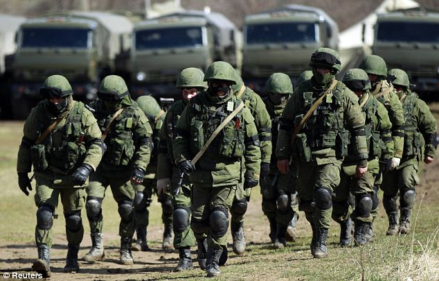 Russian might: Armed men, believed to be Russians, march at their camp near the Ukrainian military base in Perevalnoye outside Simferopol