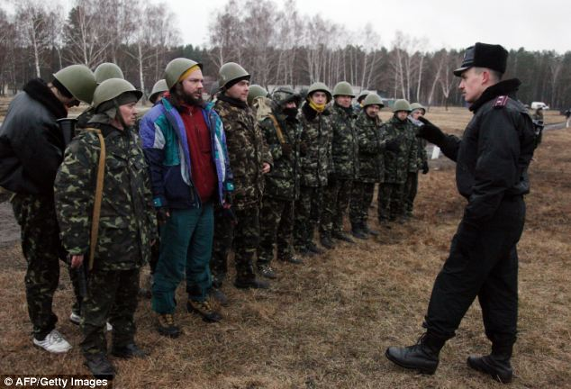 A Ukrainian interim forces officer (right) talks to recruits during their exercises not far from Kiev