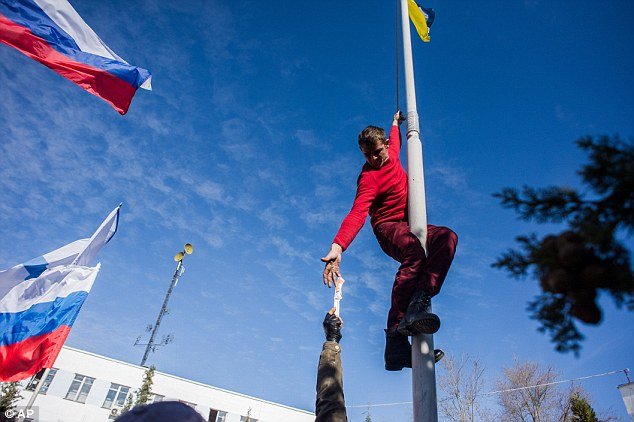 Being cut out: A member of the Pro-Russian self-defence force reaches for a knife as he takes down a Ukrainian Navy flag at the Ukrainian Navy headquarters in Sevastopol