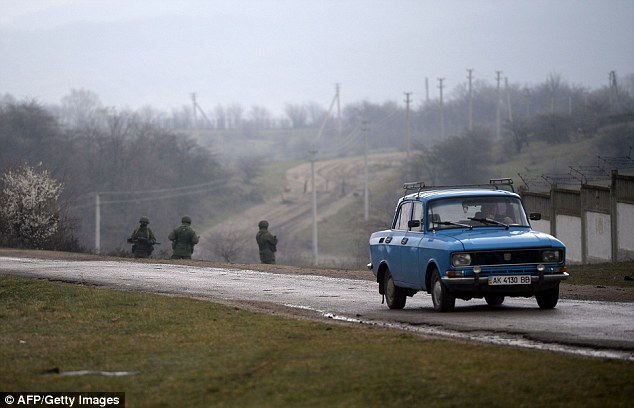 A civilian drives past Russian soldiers patrolling Perevalnoye, outside Simferopol, near a Ukrainian military base. Russian forces now control much of the region