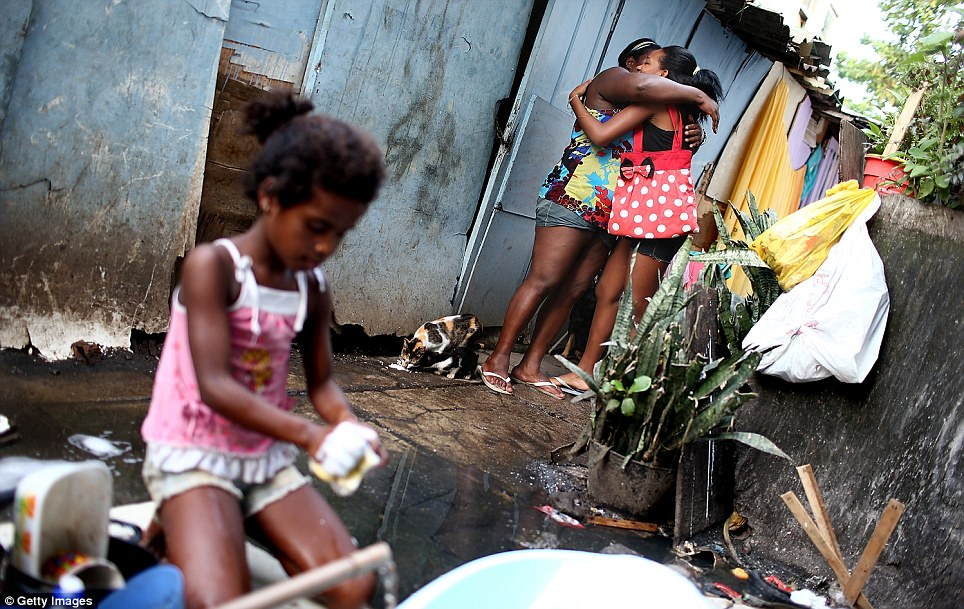 Friends hug in the complex while little Jessica washes dishes outside her home. 'Disappearances' of shanty town residents have become widespread in the police clean-up operation