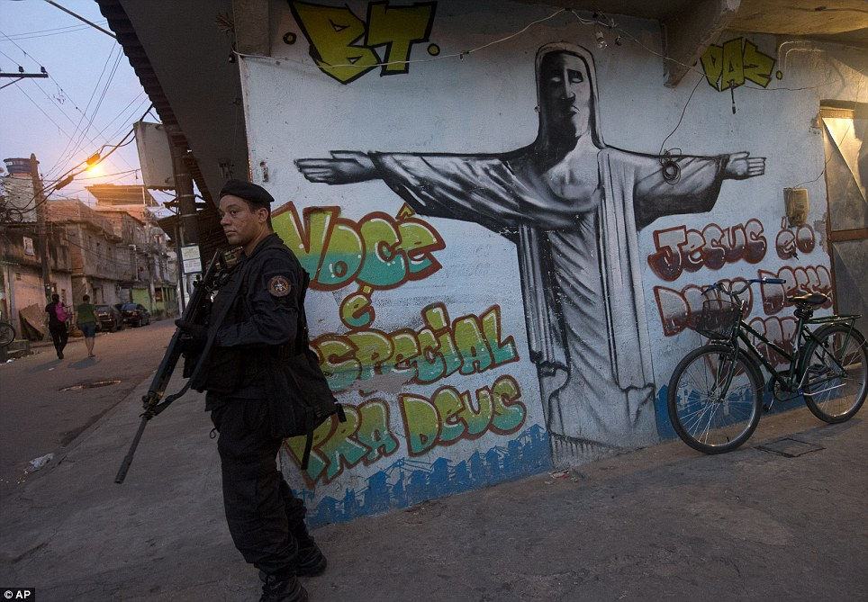 A special operations officer is pictured here in front of a graffiti drawing of Rio's symbolic statue: Christ the Redeemer. Troops have stormed the favela to rid it of drug gangs and clamp down on violence
