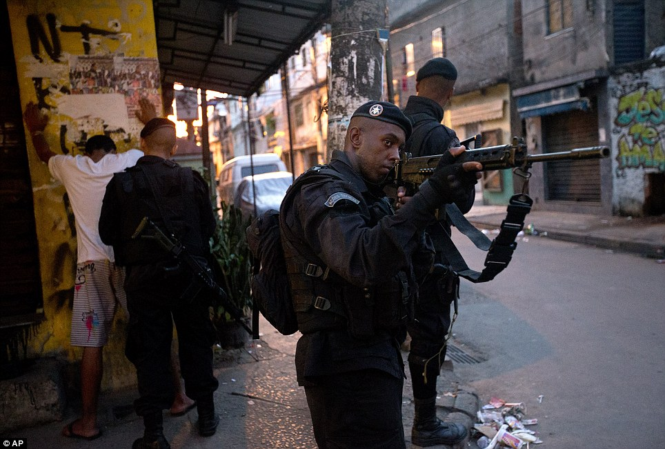 One police officer is pictured here holding a man up against a wall while he searches him. Troops took over the favela this afternoon - six weeks before the World Cup
