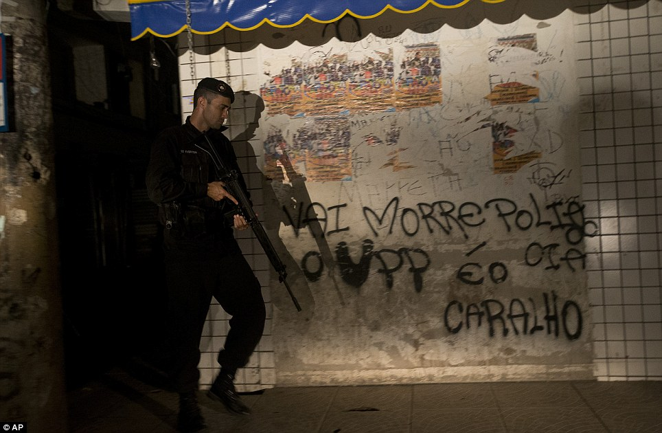 A policeman stands next to a piece of graffiti bearing the words: 'Politicians and the UPP' will die. The UPP is a special community officer group which steps in to keep peace in the favela once government troops have left