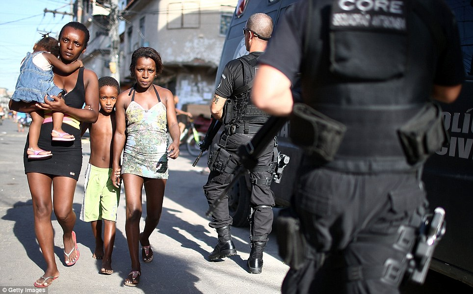 Residents are seen walking out of the favela as armed troops in bullet-proof vests storm in