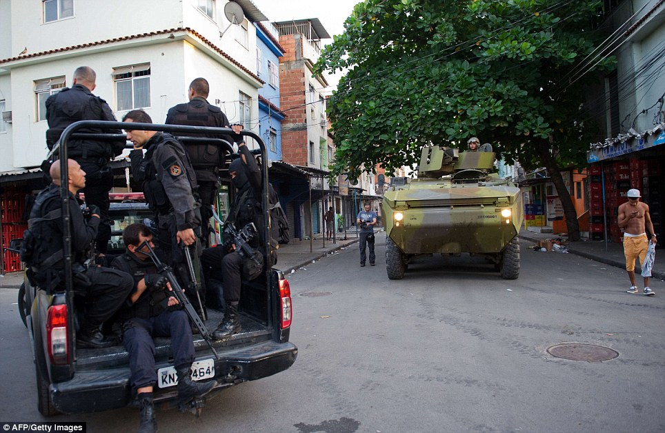 A navy tank drives behind a police van carrying scores of police officers holding machine guns