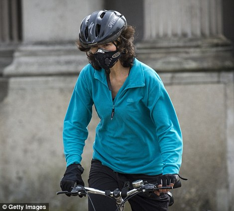 A woman wearing an anti-pollution mask rides a bicycle at Hyde Park Corner