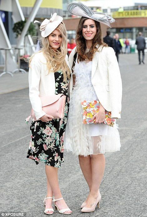 A pair of glamorously dressed racegoers