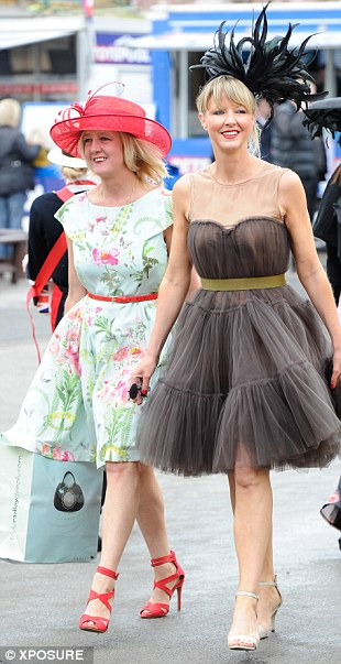 Enjoying the day: A pair of smiling racegoers arrive for a day out at Aintree