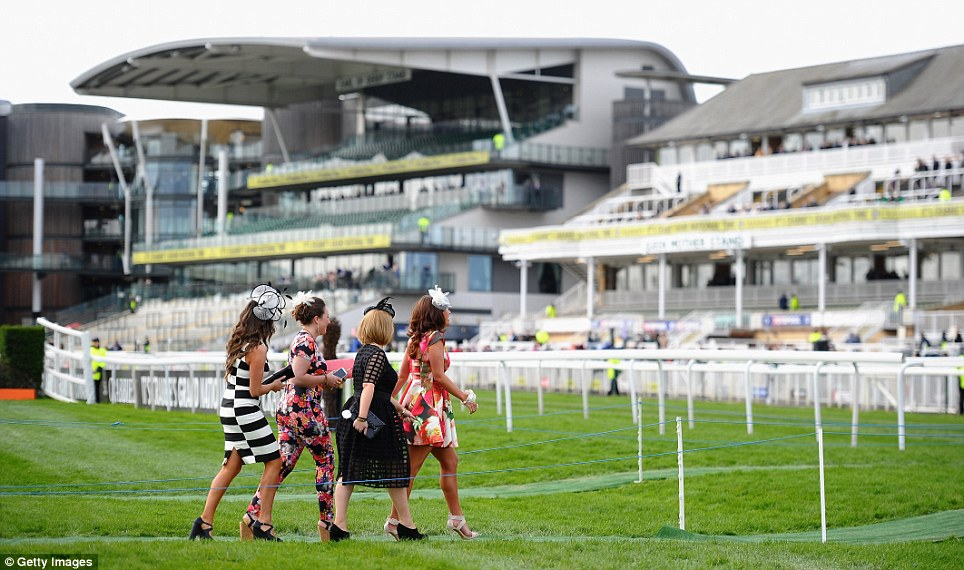 On their way: A group of racegoers pick their way across the course to the stands ahead of the racing action, which today includes the Melling Chase, at Aintree