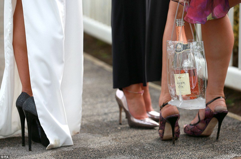 Sky-high: A group of racing fans show off their skyscraper heels as they arrive, armed with a bottle of cava, for a day at the races on Ladies Day
