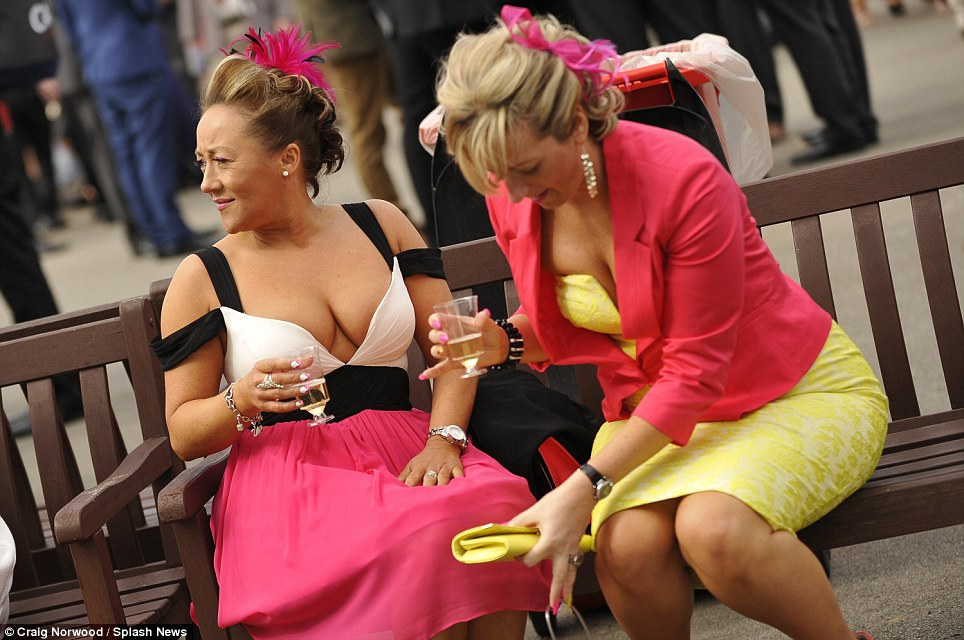 Having fun: Two racing aficionados, both of whom opted for co-ordinating cerise ensembles, relax as they enjoy the sunshine on Ladies Day at Aintree
