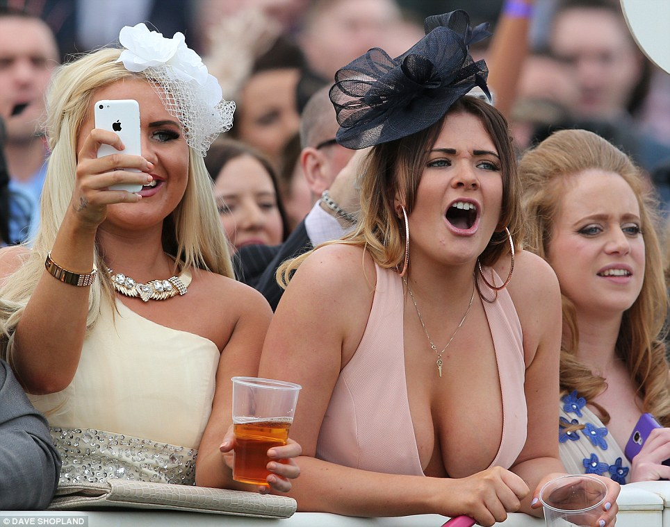 And they're off! A pair of scantily clad racegoers flash a little too much cleavage as they cheer on their chosen horses to victory at Aintree