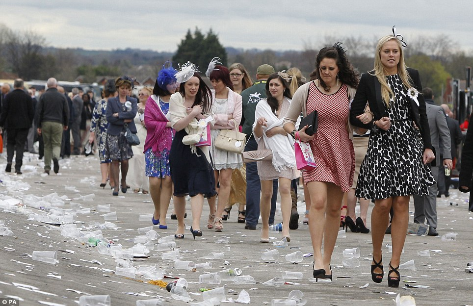 Feeling the cold: The revelers left the track as temperatures dropped at Aintree. Women hobbled through the sea of plastic cups to leave the track