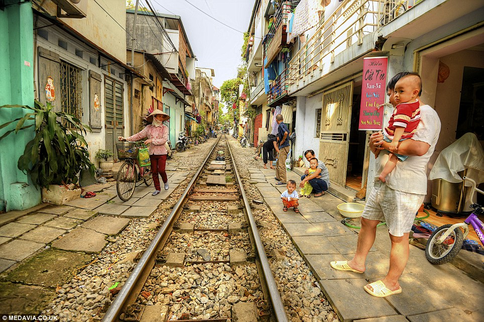 On camera: Ashit Desai, 54, of Bangalore, India, photographed the people who live next to the railway while he was on holiday in Vietnam's capital city