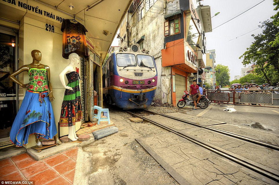 Tight space: A train squeezes past a shop display in the centre of Hanoi, Vietnam, while a man on a moped waits for the tracks to clear