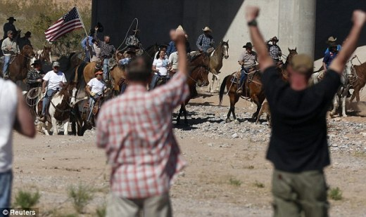 Cheers: Protesters pump their fists as cowboys herd cattle that belongs to rancher Cliven Bundy