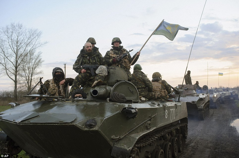 Ukrainian soldiers sit on top of military vehicles with Ukrainian national flags in a field about 44 miles from the Ukrainian town of Slovyansk, where the regional administration building was seized by pro-Russian activists
