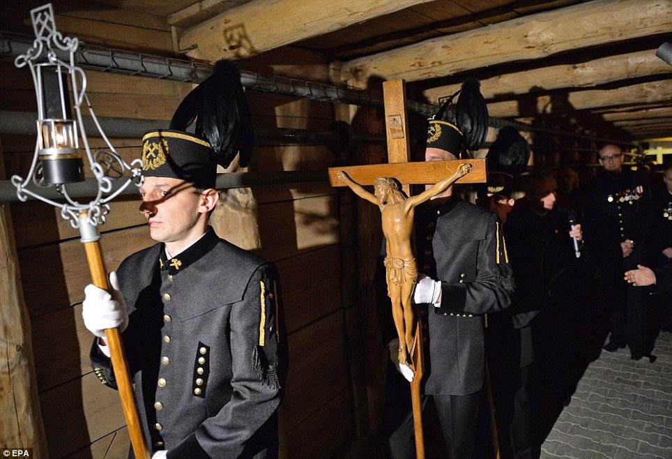 Mais profundos subterrâneos: mineiros poloneses em uniformes cerimoniais carregar uma cruz de madeira durante a Via Metro da procissão da Santa Cruz
