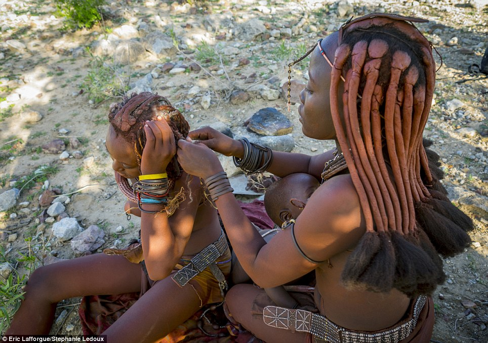 Hair today: The Himba women's elaborate hairstyles take hours to create and are lengthened by including bits of woven hay, goat hair and even hair extensions