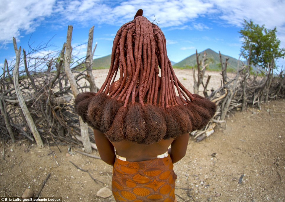 Intricate: A Himba woman shows off her long dreadlocks, created using a mixture of ground ochre, butter and goat hair. Indian hair extensions are also used