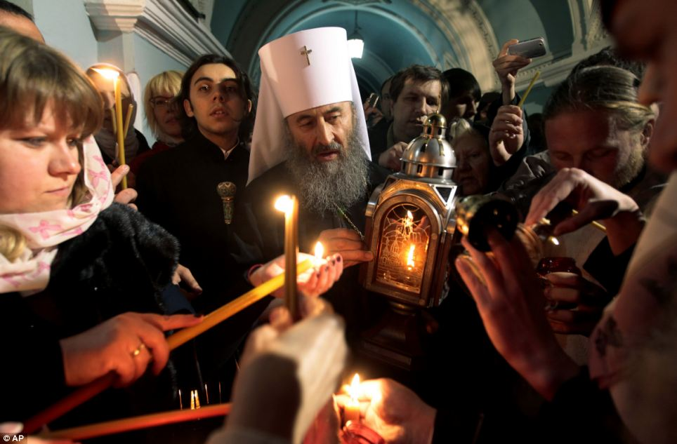 Ukrainian Orthodox believers light candles with fire brought form Jerusalem's Old City to the Kyiv-Pechersk church in the Ukrainian capital of Kiev