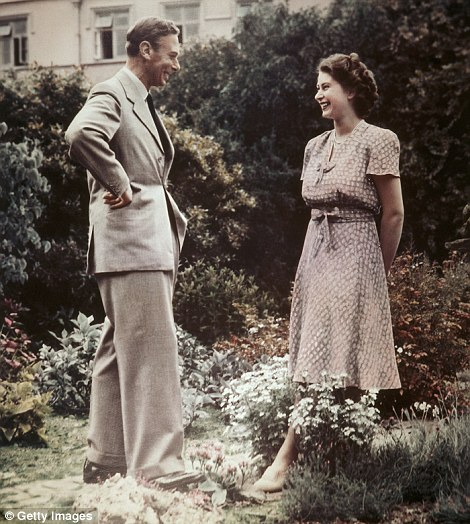 Princess Elizabeth, the future Queen Elizabeth II conversing with her father, King George VI (1895 - 1952) in a garden, 8th July 1946