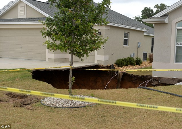 In this photo taken April 19, 2014, a sinkhole is seen between two homes, The Villages Daily Sun reports the homes were vacant when the sinkhole, which was already under repair, expanded Saturday