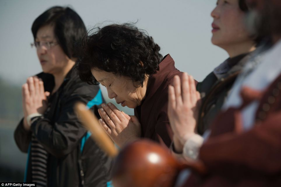 Prayers: Relatives of passengers of the capsized South Korean ferry Sewol pray in an area where family members of victims of the disaster are gathered along Jindo harbour