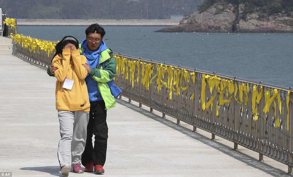 A female relative of a passenger onboard the Sewol walks down the jetty at the port in Jindo South Korea. Yellow ribbons have been tied to the barrier at the port to wish for safe return of those who are still missing