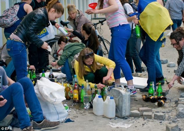 Despite the loss of life caused by fire, Ukrainian protesters prepare Molotov cocktails for their running clashes with pro-Russian activists