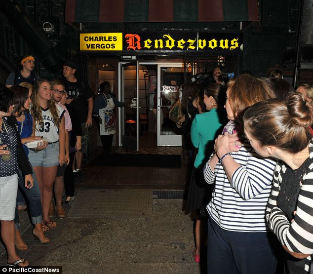Scores of people wait outside BBQ joint Rendezvous in Memphis for the arrival of the two princes
