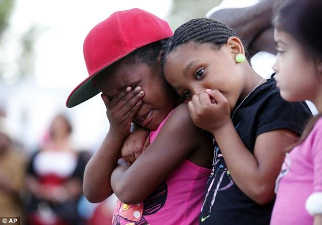 Heartbreaking: Children weep during a prayer vigil for Martin Cobb on Saturday