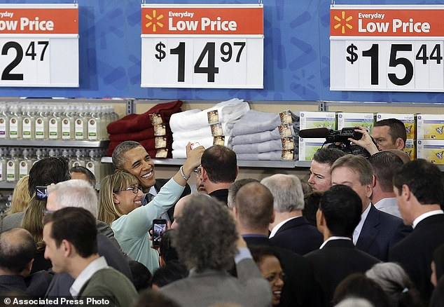President Barack Obama poses for a photo after speaking at a Walmart store in Mountain View, California on Friday
