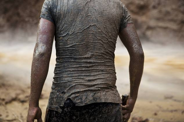 In this May 4, 2014 photo, a miner continues his search for gold in mud-drenched clothes inside a crater at an illegal gold mine process in La Pampa in Peru'...