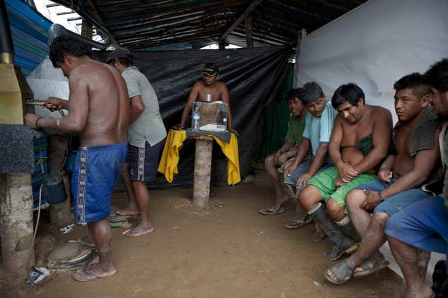 In this May 3, 2014 photo, wildcat miners wait their turn to melt their amalgam of gold and mercury to burn off the mercury in the temporary home of a gold b...