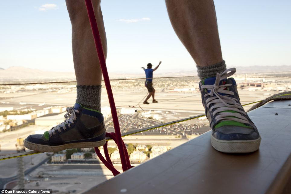 Any Lewis puts one foot on the line and another on a ledge as he prepares to set off on another daredevil crossing. Meanwhile another expert crosses in the background holding his arms out wide for extra balance