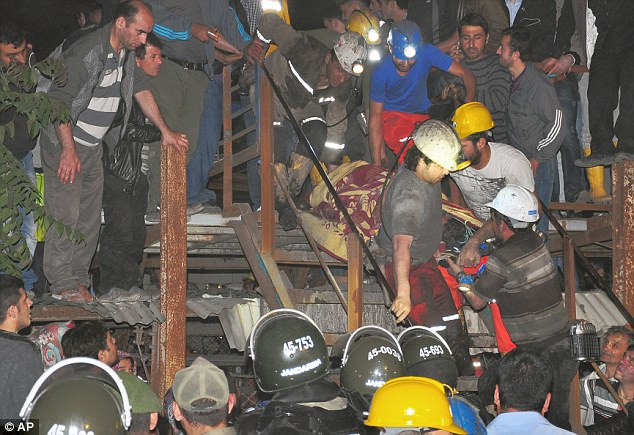 Miners carry a friend to safety - but around 300 workers were still trapped on Wednesday morning