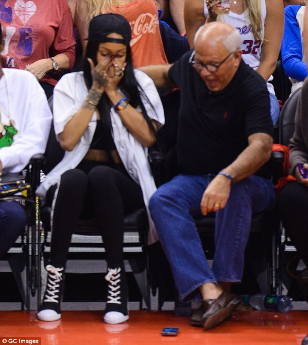 Whoops: Rihanna looks dismayed after dropping Los Angeles Police Commission President Steve Soboroff's phone during a basketball match last Friday after the pair took a selfie