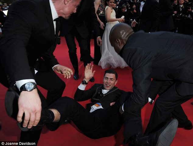 Unruffled: The prankster didn't appear to care about his undignified stunt, laughing as he was removed from the carpet