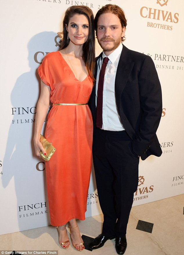 Striking: Felicitas Rombold stood out in an orange dress as she and Daniel Bruhl arrived at the event