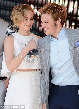 She's pleased: The actress shares a joke with hunky co-star Sam Claflin