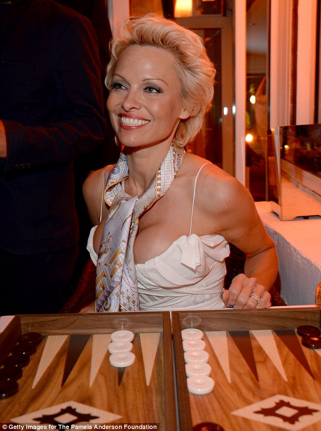 Belle of the ball: Pam looked right at home as she posed for a photo behind one of the backgammon boards, looking Old Hollywood glamorous with her cropped platinum tresses styled back from her face, which was beautifully made up with dewy golden skin, rose lips and smoky eyes