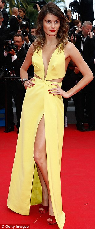 Leggy: Natasha Poly, left, showeed skin in a see-through black gown, as  Isabeli Fontana, right, dislayed her lean limbs in a sleeveless yellow dress with a thigh-high-slit