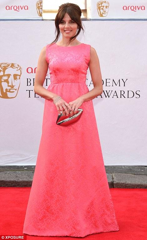 Pretty in pink: Ophelia Lovibond war a vintage-inspire brocade dress and carried a Lulu Guinness lip-shaped clutch bag