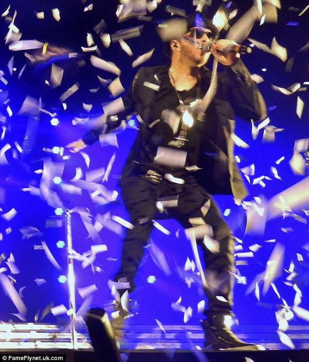 Making it rain! The singer stomped his feet and stayed in rhythm as confetti streamed over him in a performance in Paris on Sunday