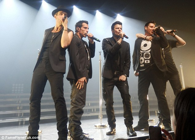 Old friends: Wahlberg wrapped an arm around Jonathan Knight mate as the five-some sang to the crowd in Paris on Sunday