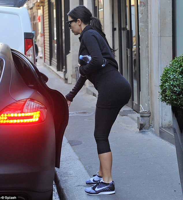 Ready to go: Kim climbs into a waiting car after visiting a French gym on Monday