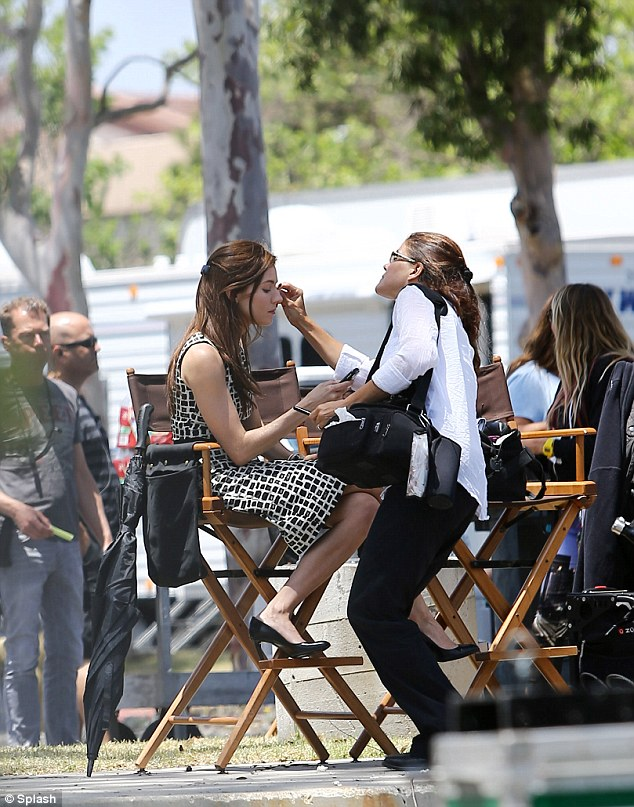 Catching up on emails: She looked at her smart phone while getting touched up by the make-up artist